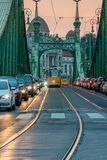 Autos und Trams bei Sonnenuntergang auf Liberty Bridge in Budapest Ungarn stockfoto