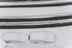 Autos unter Schnee auf einem Parkplatz in der Straße während der Winterschneefälle Stockfotos