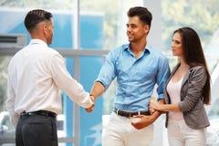 Autosalon Junges Paar trifft Verkäufer im Selbstsalon Lizenzfreie Stockfotos