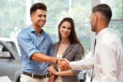 Autosalon Junges Paar trifft Verkäufer im Selbstsalon Lizenzfreie Stockbilder