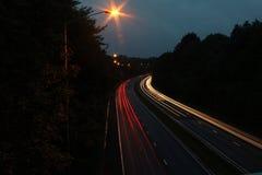 Autoscheinwerfer auf Autobahn Stockfotografie