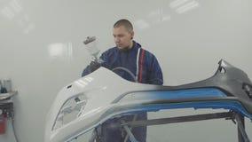 Autoschilder die witte verf op auto voorbumper bespuiten in speciale cabine stock videobeelden