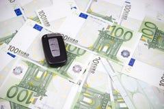 Autoschlüssel auf einem Hintergrund des Euros Lizenzfreie Stockbilder