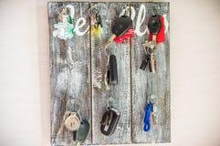 Autoschlüssel, die am hölzernen Brett hängen lizenzfreie stockfotografie