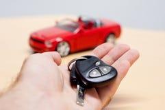 Autoschlüssel mit Schattenbild eines konvertierbaren Cabrioletautos Lizenzfreie Stockfotografie