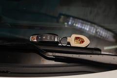 Autoschlüsselferntüröffner mit einem ledernen keychain von Porsche Cayman, das auf der Windschutzscheibe an den Wischern liegt stockfoto