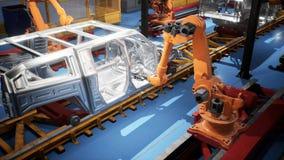 Autoschweißenslinie des Förderers mit Rahmen von unfertigen Autos und von Roboterschweißern stock video footage