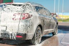 Autoservicio del túnel de lavado El dueño lava su coche foto de archivo
