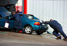 Autoshop and broken car. Workers pushing the car to autoshop Stock Images