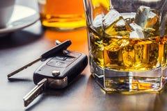 Autosleutels en glas van alcohol op lijst stock afbeeldingen