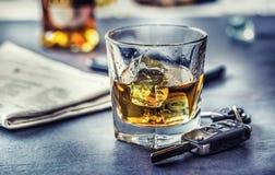 Autosleutels en glas van alcohol op lijst in bar of restaurant stock fotografie