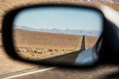Autospiegel, door een auto in de woestijn, paranoia wordt gevolgd die Stock Foto