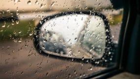 Autospiegel door glas met regendruppels stock afbeelding