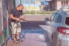 Autosserviço da lavagem de carros O proprietário lava seu carro imagem de stock