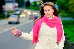 Autostop de la muchacha en la carretera Imagenes de archivo