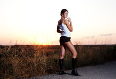 Autostop model on sunset. European model posing on the road Royalty Free Stock Photo