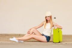 Autostopista de la mujer con la maleta que se sienta en el camino Foto de archivo libre de regalías