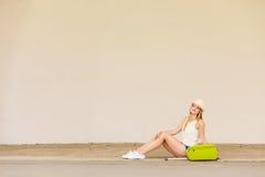 Autostopista de la mujer con la maleta que se sienta en el camino Fotos de archivo