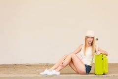 Autostopista de la mujer con la maleta que se sienta en el camino Fotos de archivo libres de regalías