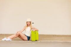 Autostopista de la mujer con la maleta que se sienta en el camino Fotografía de archivo libre de regalías