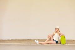Autostopista de la mujer con la maleta que se sienta en el camino Imágenes de archivo libres de regalías