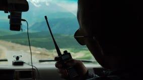 Autostopista del salvador con la maleta anaranjada que para el coche en el camino de la montaña almacen de video