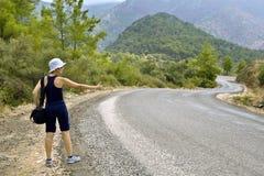Autostopista en el camino en montañas fotografía de archivo libre de regalías