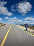 Autostoppista delle donne sulla strada al giorno soleggiato idilliaco Fotografia Stock Libera da Diritti