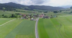 Autostrada attraverso il villaggio del campo e di verde alle montagne archivi video
