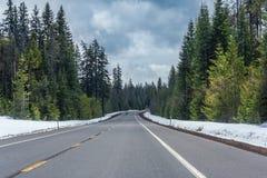 Autostrada bieg przez lasów Oregon zakrywał z śnieżnym usa Fotografia Stock