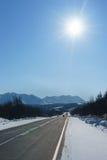 Autostrada góra wśród śniegu i lód przy zima czasu ander niebieskim niebem Fotografia Stock
