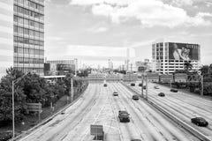 Autostrada lub jezdnia z samochodami i drapaczami chmur na chmurnym niebieskim niebie Droga z ruchów drogowych znakami dla przewi zdjęcie royalty free