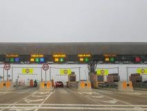 Autostrada pagata illuminata di giorno in giorno, con nebbia fotografia stock