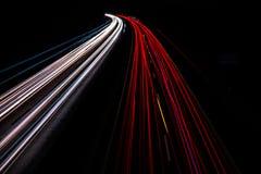 Autostrada przy nocą z szybkimi poruszającymi samochodami zdjęcie stock