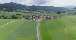 Autostrada a través del pueblo del verde y del campo a las montañas almacen de video