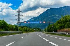 Autostrada w górach z drogowego znaka wzrosta kontrolą w niemiec w Alps, Austria obraz royalty free