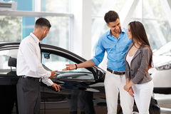 Autotoonzaal Jong Paar die een Nieuwe Auto kopen bij het Handel drijven Stock Fotografie