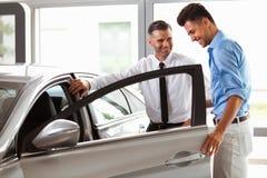 Autotoonzaal Voertuighandelaar die Jonge Mens Nieuwe Auto tonen stock foto