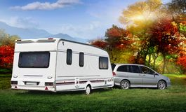 The autotrailer stands on a vedic lawn lawn in the forest with a view of the mountains. Early autumn with red and delta trees. The royalty free stock photos