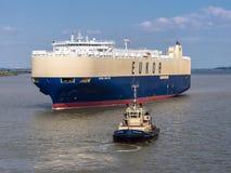 Autotransporter-Schiff und Tug Boat Stockbild