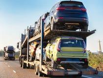 Autotransporter trägt Autos entlang der Landstraße lizenzfreies stockfoto