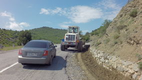 Autotravel Summer south of Crimea. Tractor removes rockfall on the road. Autotravel Summer south of the Crimea. Tractor removes rockfall on the road stock video footage