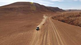 Autotravel: un coche negro grande se mueve adelante a través del camino de la arena metrajes