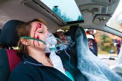Autounfall - Opfer im Unfallfahrzeug, das erste Hilfe empfängt Lizenzfreies Stockbild