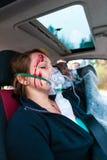 Autounfall - Opfer im Unfallfahrzeug, das erste Hilfe empfängt Stockfotografie
