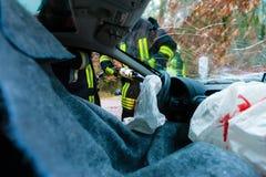 Autounfall - Opfer im Unfallfahrzeug, das erste Hilfe empfängt Stockfoto