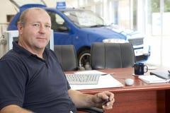 Autoverkäufer, der im Ausstellungsraum sitzt Stockbild