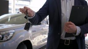 Autoverkaufverkaufszentrum, Berufsautoverkäuferkerl hält in den Handschlüsseln zum neuen Automobil für Verkauf in der Verkaufsste stock video footage