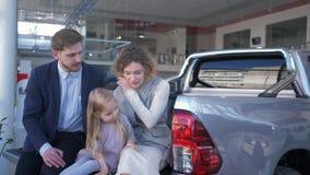 Autoverkaufverkaufszentrum, junge Paare mit Kind wählt Automobil und ist einander beim Sitzen im Stamm an verbunden stock video footage