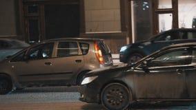 Autoverkeer bij de stadsstraat van de de winternacht tijdens sneeuwval stock video
